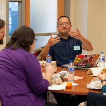 Man speaks with expressive arm movements surrounded by other scholars at a table.