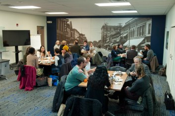 Wide shot of scholars discussing amongst themselves at four different tables.