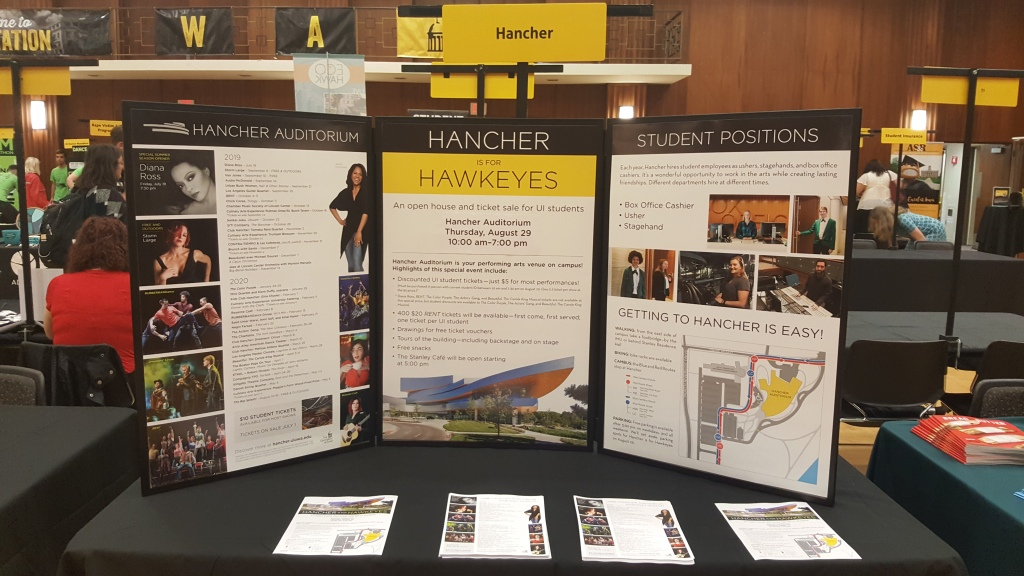 The image shows a standup poster of the entire Hancher schedule, along with an add for Hancher is for Hawkeyes and student employment opportunities. This was taken while tabling at UI Orientation.