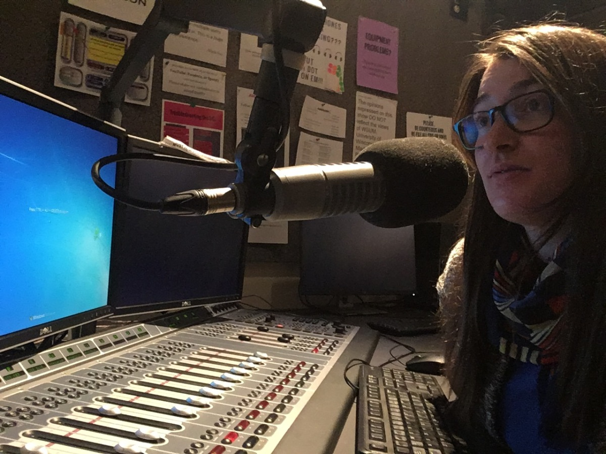 Laura Perry sitting at a microphone and audio board at a recording studio or radio station.